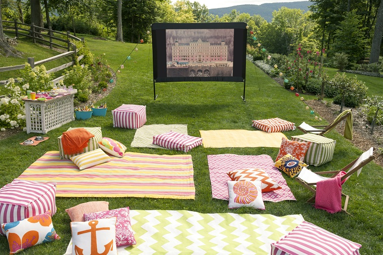 Giardino con prato verde, tv schermo da aperto, addobbi per festa di compleanno