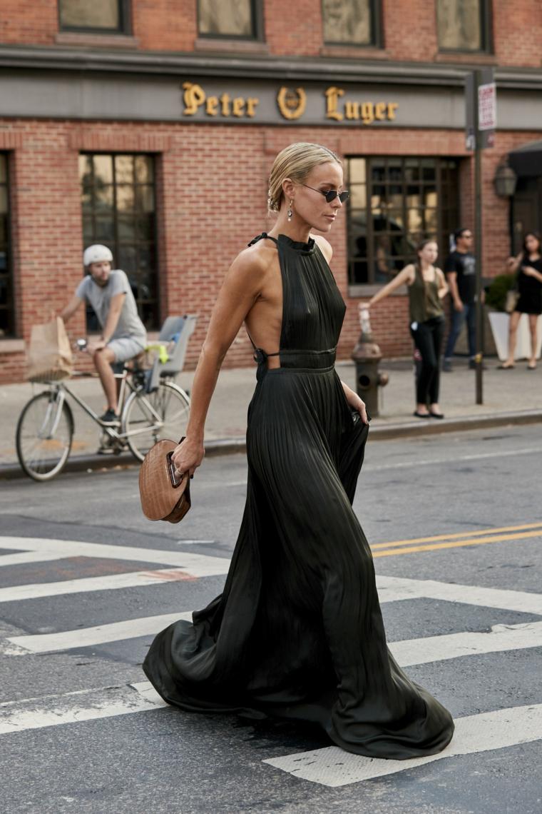 Abiti eleganti per signora, vestito nero plissettato, donna che attraversa la strada