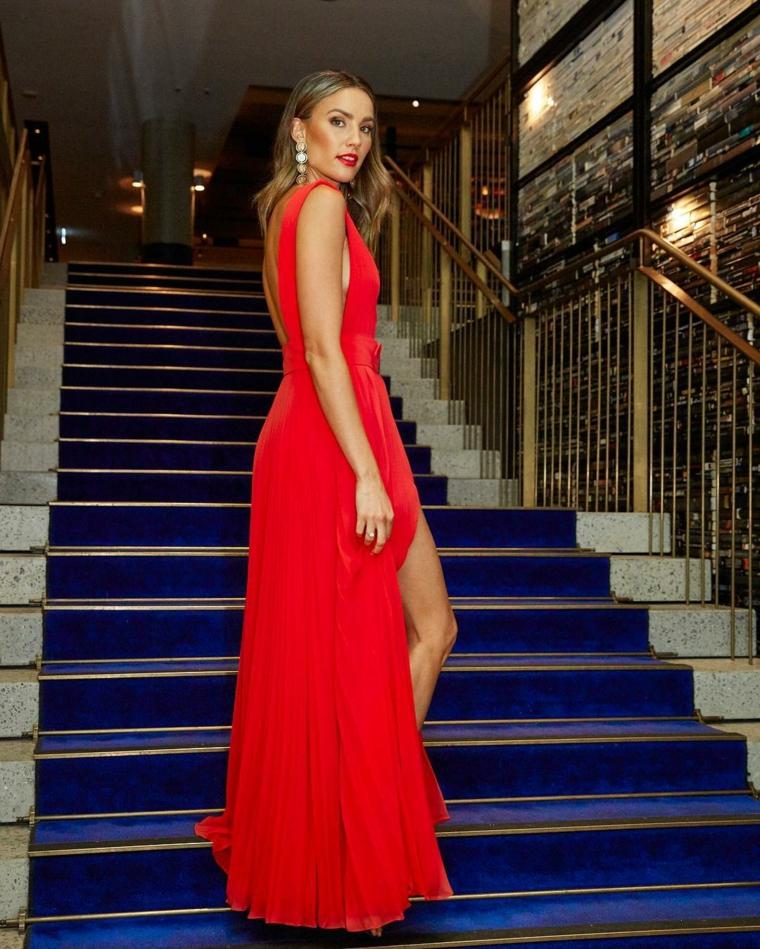 Abiti eleganti per signora, vestito rosso con spacco, abito con schiena scoperta, ragazza che sale le scale