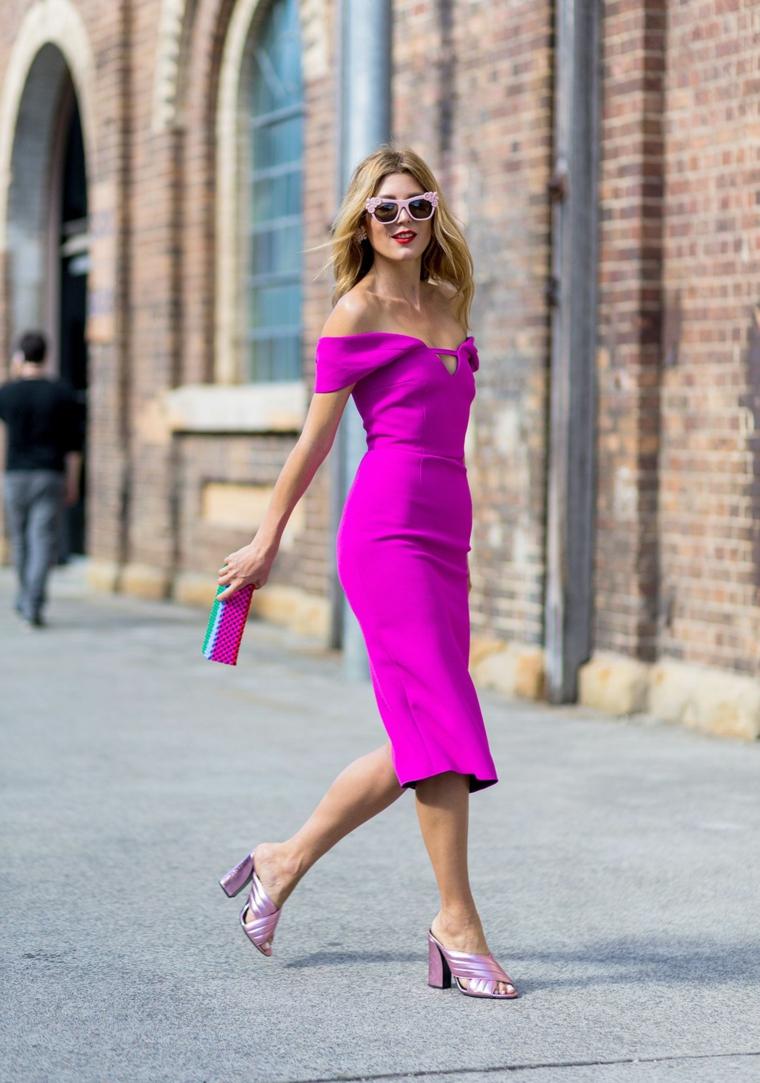 Vestito viola con spacco, donna che cammina, abito con capelli biondi, occhiali da sole rosa