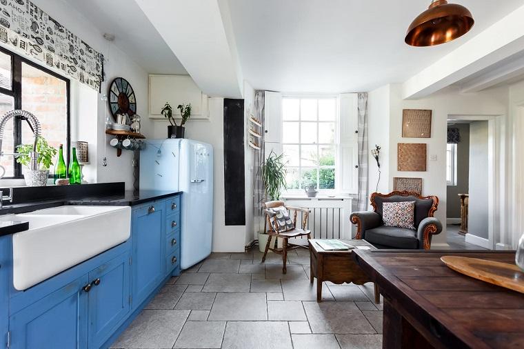 Cucina con mobili di legno, mobili di colore blu, tavolo di legno, frigo azzurro Smeg