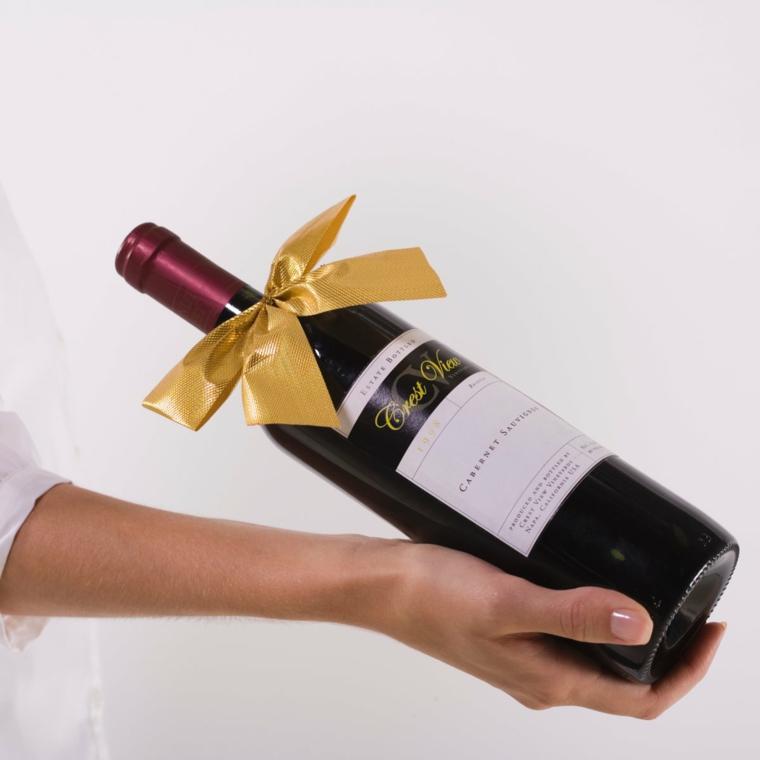 Regalini natalizi, bottiglia di vino, bottiglia decorata con nastro, il braccio di una donna