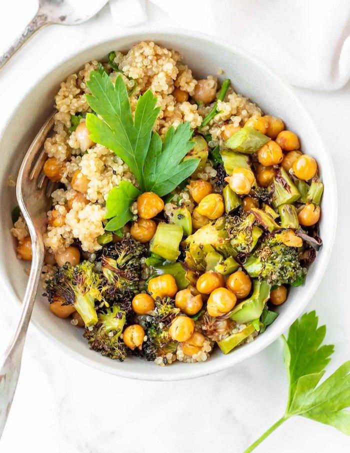 Piatto con ceci, quinoa e broccoli, foglie di prezzemolo, cena sfiziosa e veloce per amici