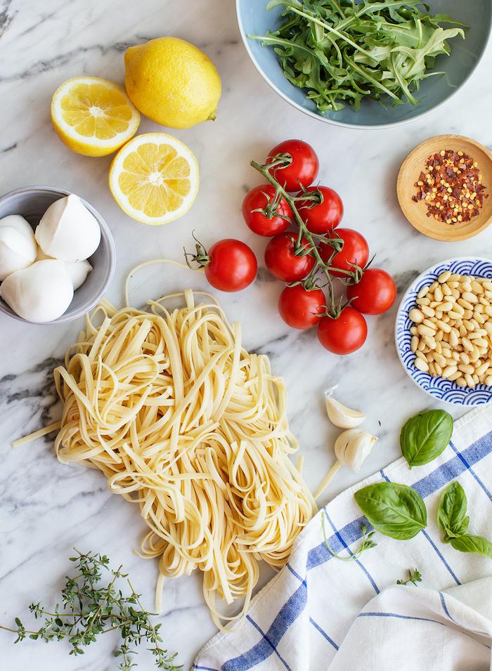 Ingredienti su un tavolo di marmo, rametto di pomodorini, foglie di basilico, ricette facili per cena