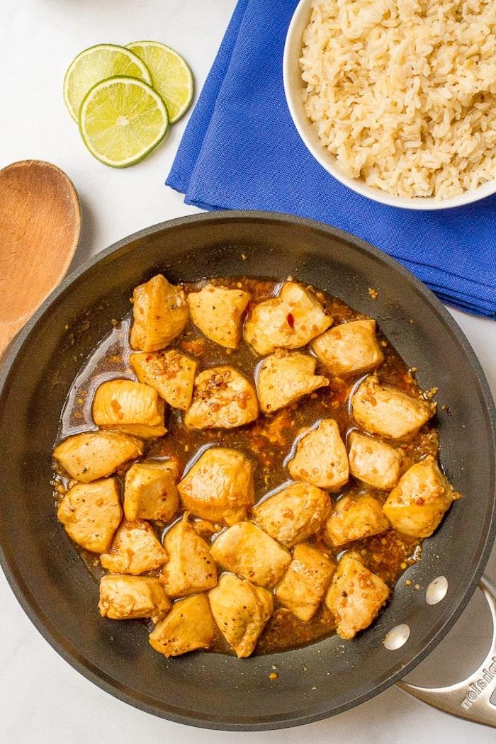 Padella con bocconcini di pollo, ciotola con riso in bianco, fette di limone, cosa cucino stasera