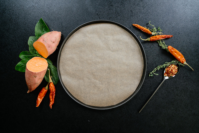 Teglia ricoperta con carta da forno, patata tagliata in due, patate dolci, idee per cena leggera