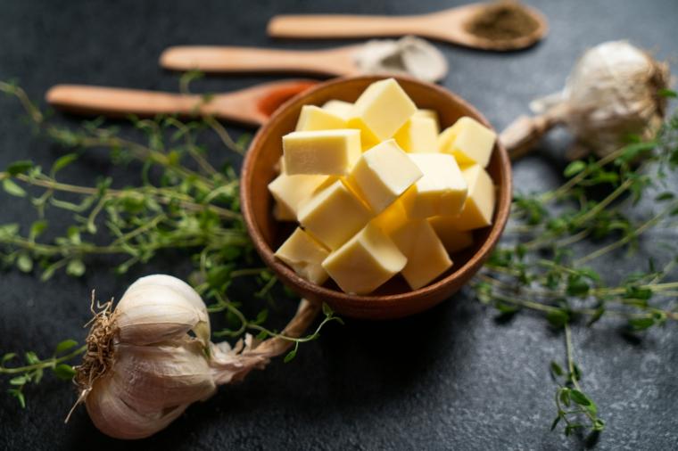 Ciotola di legno con cubetti di burro, ricetta per patata a fisarmonica