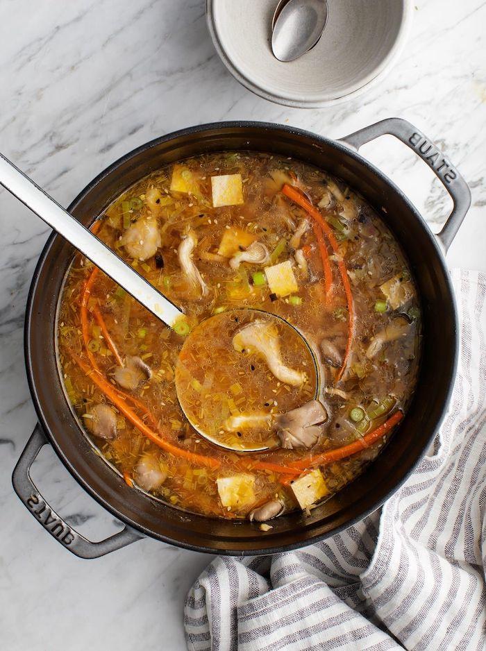 Pentola con minestra di funghi, mestola con zuppa, cena sfiziosa e veloce per amici