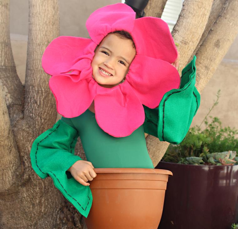 Vestiti carnevale bambina, bimba travestita da fiore, pianta con foglie rosa, vaso di plastica