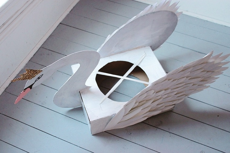 Cigno di cartone, cigno con corona glitter, vestiti carnevale bambina, pavimento in legno