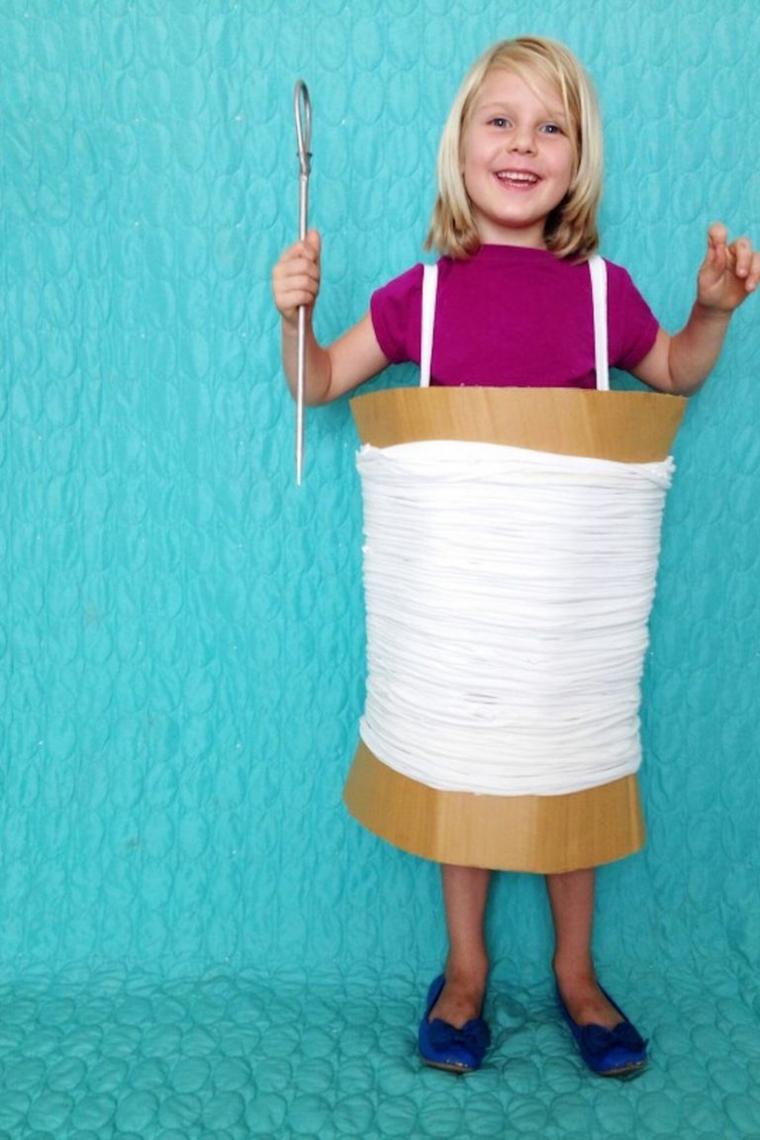 Costume carnevale improvvisato, bimba con grembiule fai da te, cartone e filato bianco