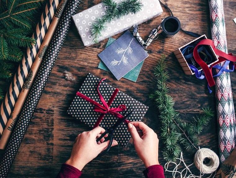 Incartare un regalo, regalini per un uomo, rametti verdi e spago, rotoli di carta natalizia