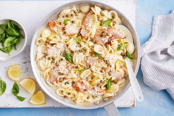 Orecchiette al sugo di formaggi, fette di limone, foglie di basilico, padella con pasta, cena sfiziosa