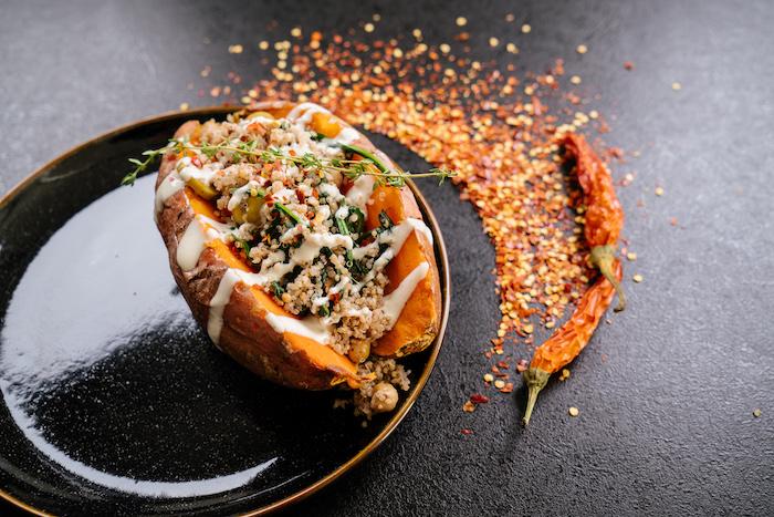 Cena sfiziosa, patata dolce con ripieno, peperoncino rosso secco, ripieno di quinoa e salsa bianca