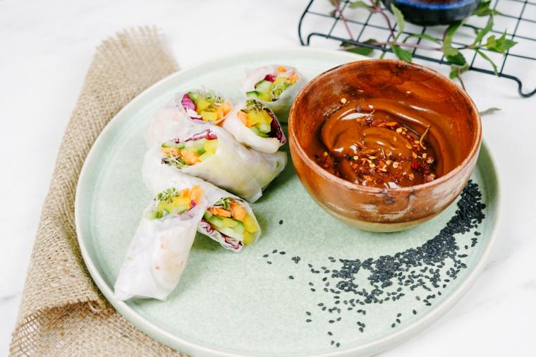 Piatto con involtini primavera, ciotola di legno con salsa di burro di arachidi