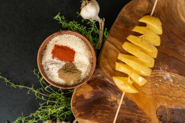 Imburrare le patate hasselback, ciotola di legno con parmigiano grattugiato e spezie