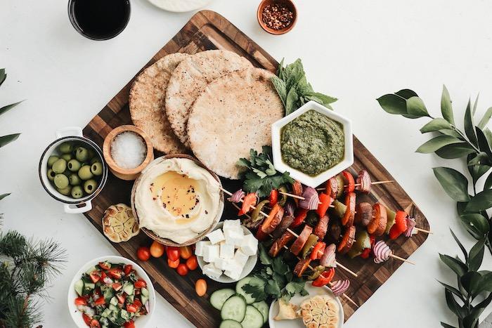 Spiedini di verdure, piadine di pane integrale, ciotole con olive, cena leggera invernale