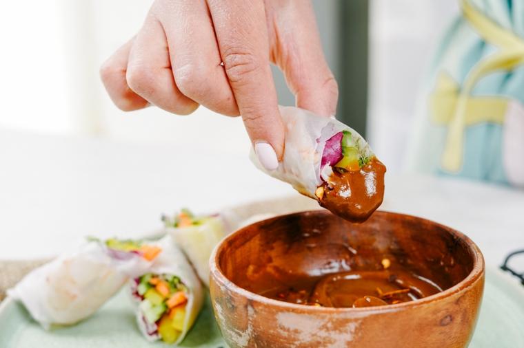 Immergere gli involtini nella salsa, involtini con carta di riso e verdure