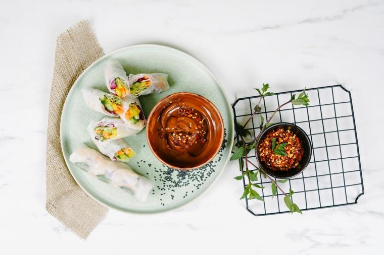 Piatto con involtini primavera e ciotola con salsa, avvolgere verdure nella carta di riso
