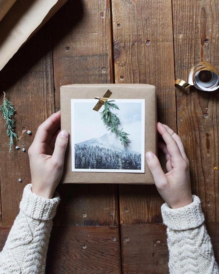 Pacco regalo con foto, tavolo di legno, nastro di colore oro, rametti verdi, regali originali per lei