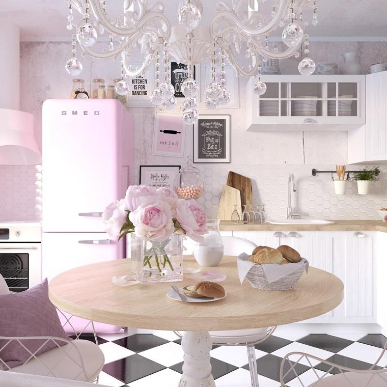 Pavimento cucina a scacchi, lampadario in cristallo, frigo rosa Smeg, tavolo di legno rotondo