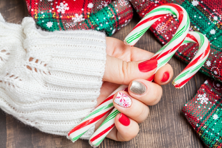Due bastoncini natalizi di zucchero, unghie rosse eleganti, accent nails con disegni
