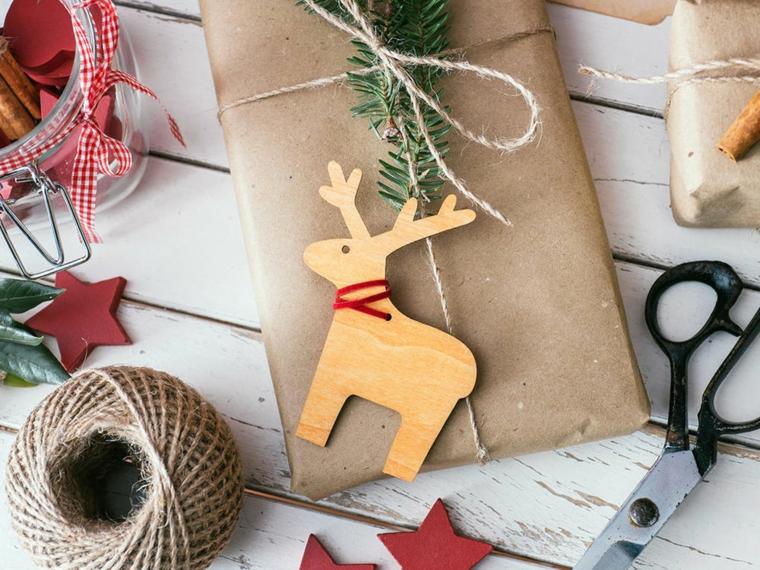 Regalo incartato con spago, renna di legno, rotolo di spago, tavolo di legno, regalo natalizio