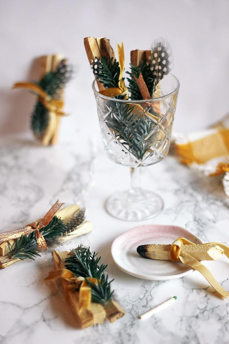 Cosa farsi regalare a Natale, calice di vetro, palo santo decorato, rametti di pino e piume