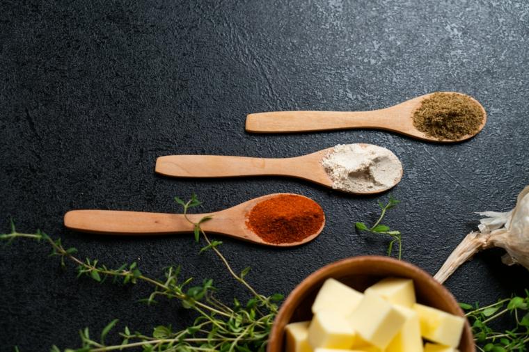 Tre cucchiai di legno con spezie, ingredienti per patata a ventaglio