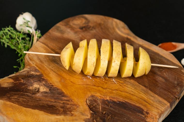 Patate al forno particolari, tagliere di legno con patate, ingredienti per patate al forno