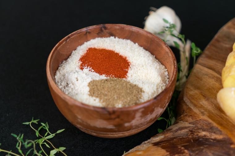 Patata a fisarmonica, ciotola di legno con parmigiano grattugiato e spezie