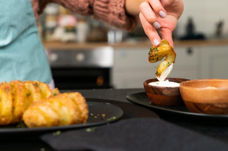 Patata a fisarmonica immersa in una ciotola con maionese, piatto con patate al forno