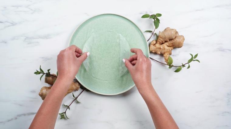 Le mani di una donna che immerge la carta di riso, radici di zenzero e foglie di menta