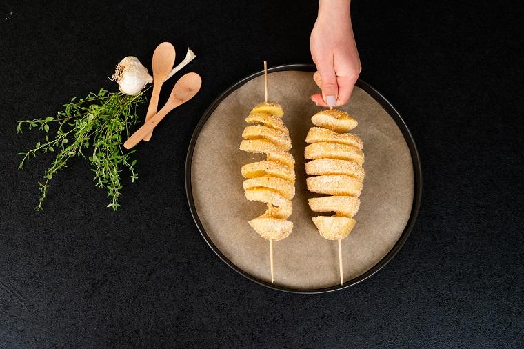 Patate al forno particolari, due patate a fisarmonica con timo fresco