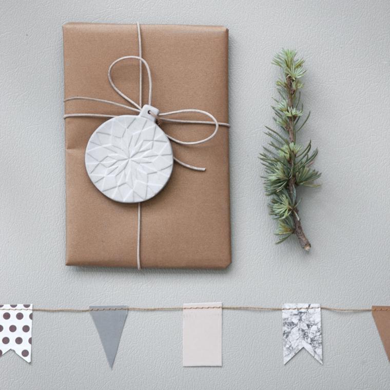 Ghirlanda con pezzettini di stoffa, pacco regalo incartato, rametto di pino