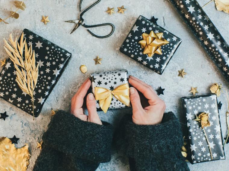 Regali per fidanzato natale, scatole incartate, forbici e sticker natalizi, mani di una donna