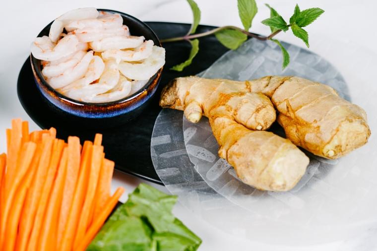 Piatto con carta di riso e zenzero, ciotola con gamberi saltati in padella