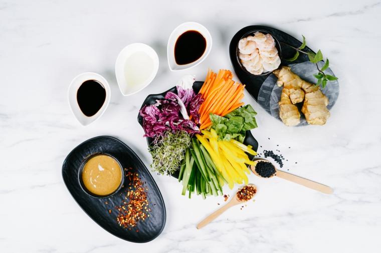 Piatti con verdure tagliate a julienne, ingredienti per fare gli involtini primavera