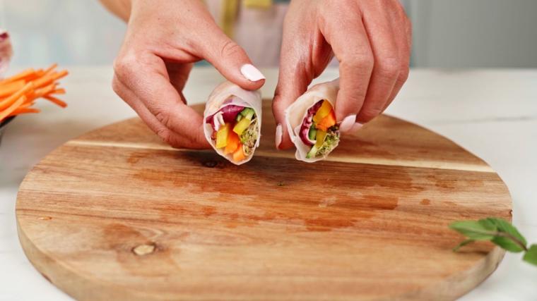 Tagliere di legno con involtini primavera, avvolgere le verdure nella carta di riso