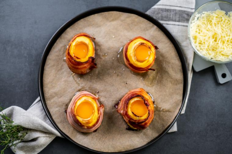 Ricette facili con patate, teglia con patate avvolte in bacon e ripieno di uova
