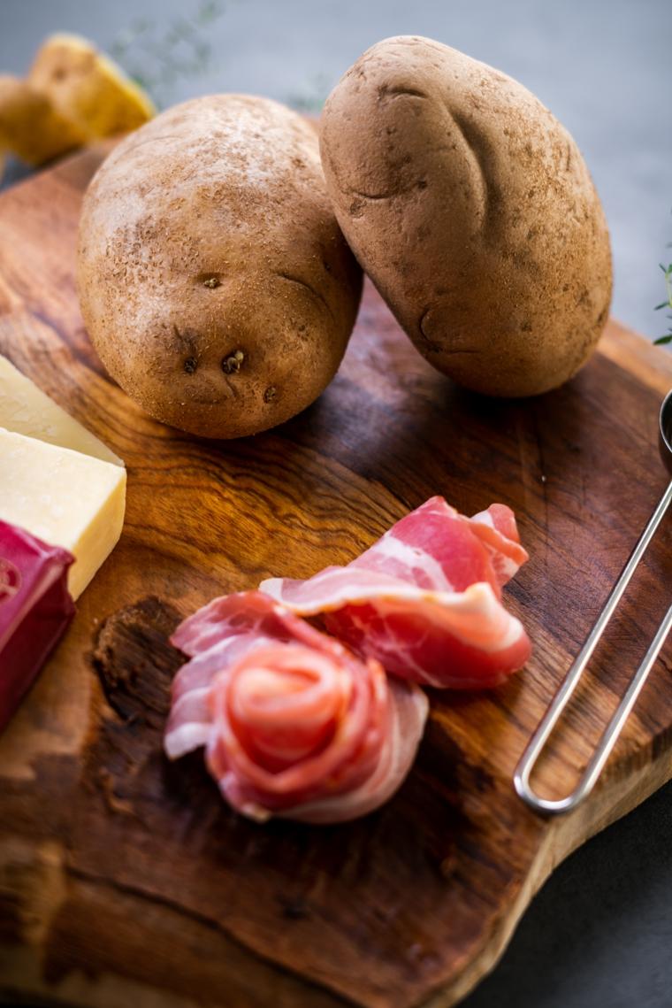 Due patate e fette di bacon, ricette con patate, tagliere di legno ingredienti sopra