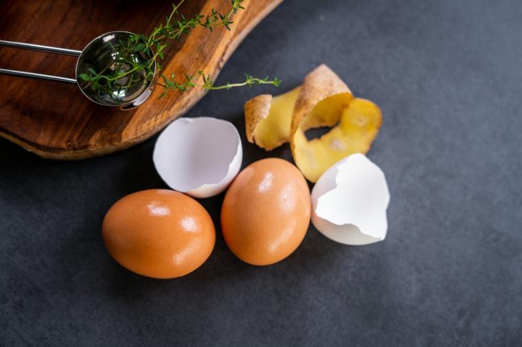 Buccia di patate e due uova, ricette con uova e patate, tagliere di legno con erbette