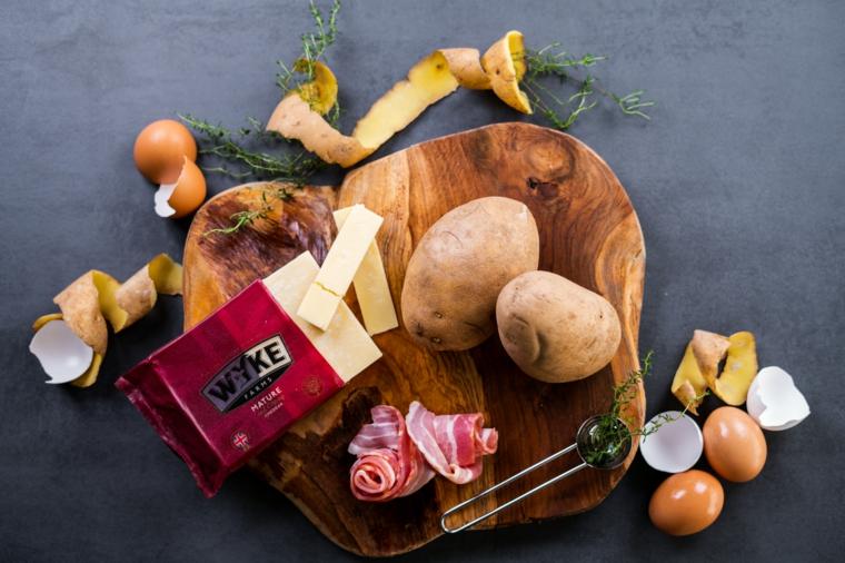 Ingredienti su un tagliere di legno, ricette con patate, formaggio e fette di bacon