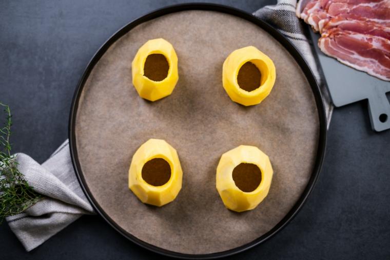 Quattro patate sbucciate e tagliate, ricette con patate al forno, teglia rotonda con carta da forno