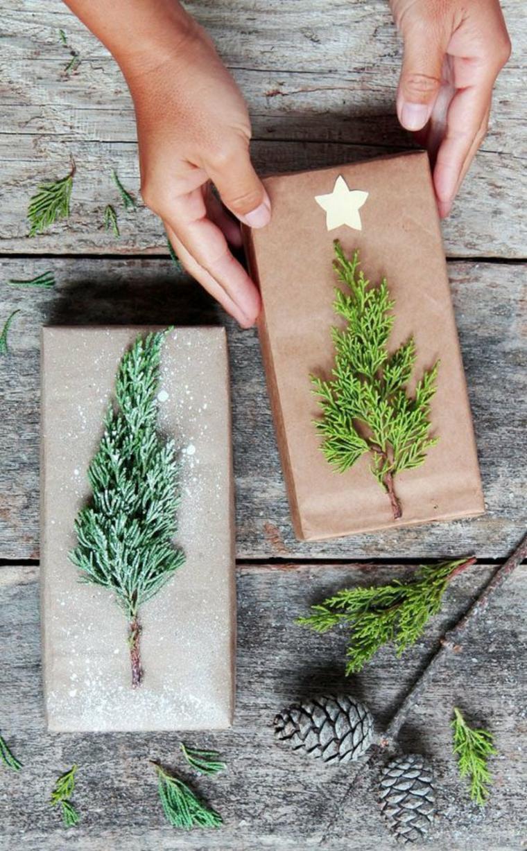 Scatola regalo decorata, rametti verdi e pigne, regali di Natale per lui