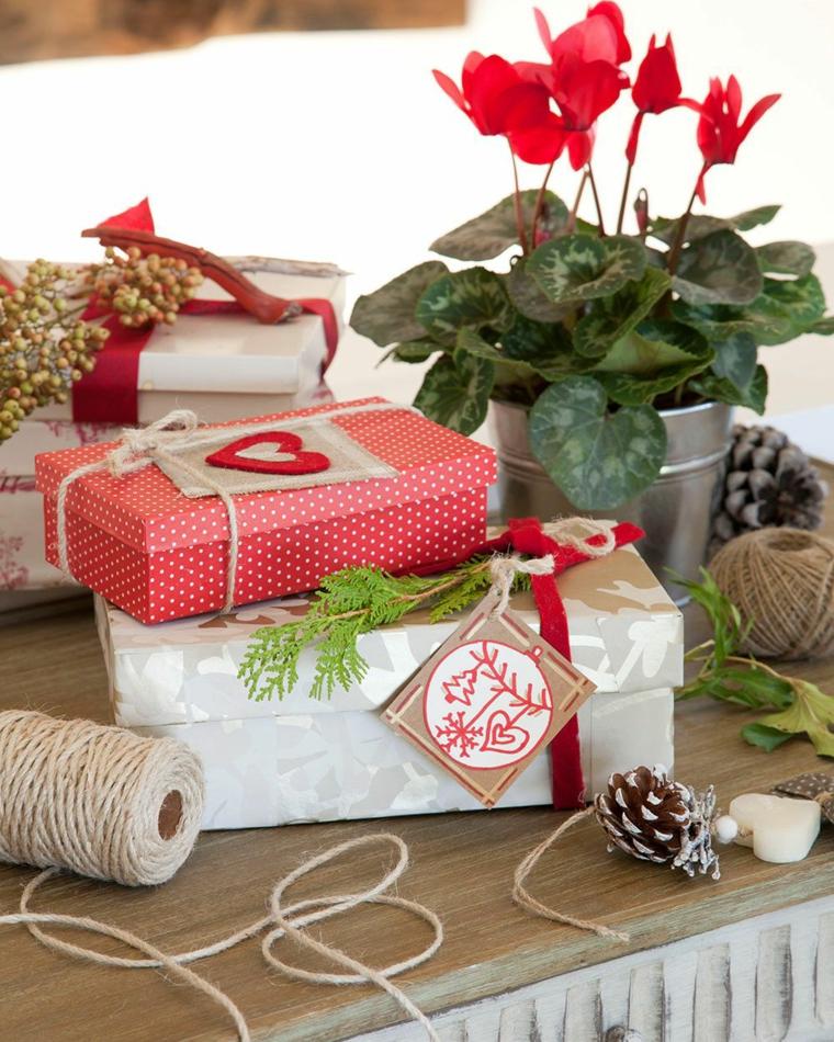 Scatole regalo incartate, vaso di pianta, pigne e spago, decorazioni regalo per donna