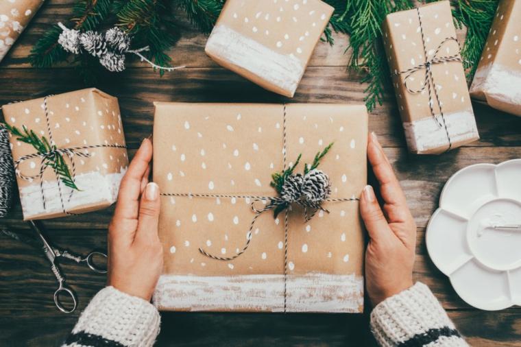 Cosa regalare alla mamma per Natale, scatola regalo incartata, pigne e rametti verdi