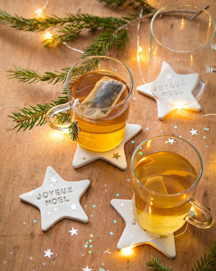 Sottobicchieri con scritte, tazze di tè, rametti verdi, cosa farsi regalare a Natale, filo di lucine