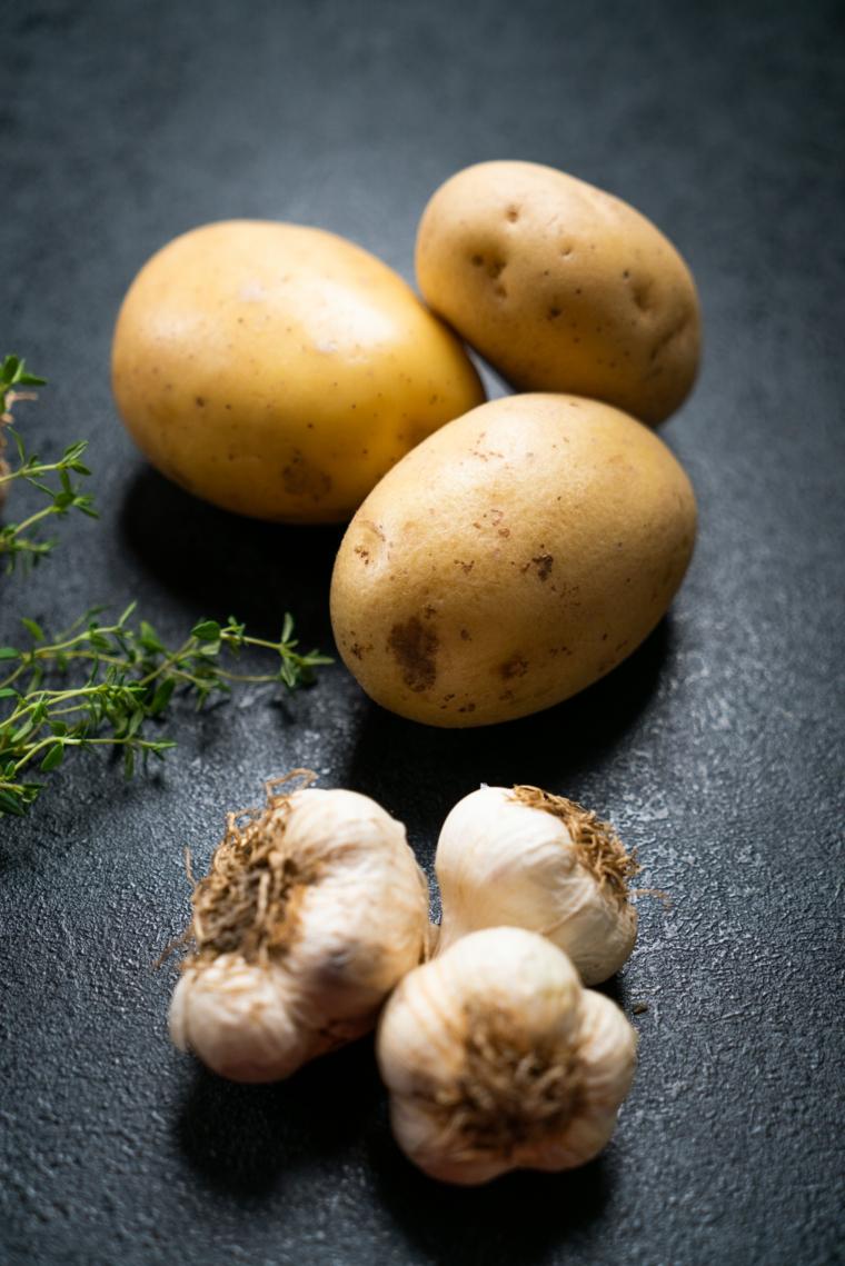 Patate al forno particolari, tre patate con le bucce e tre teste di aglio