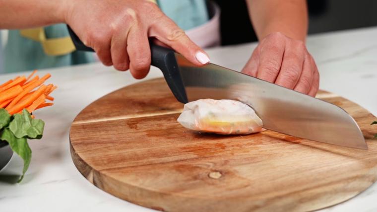 Tagliare con un coltello gli involtini primavera, piatto con verdure tagliate sottili